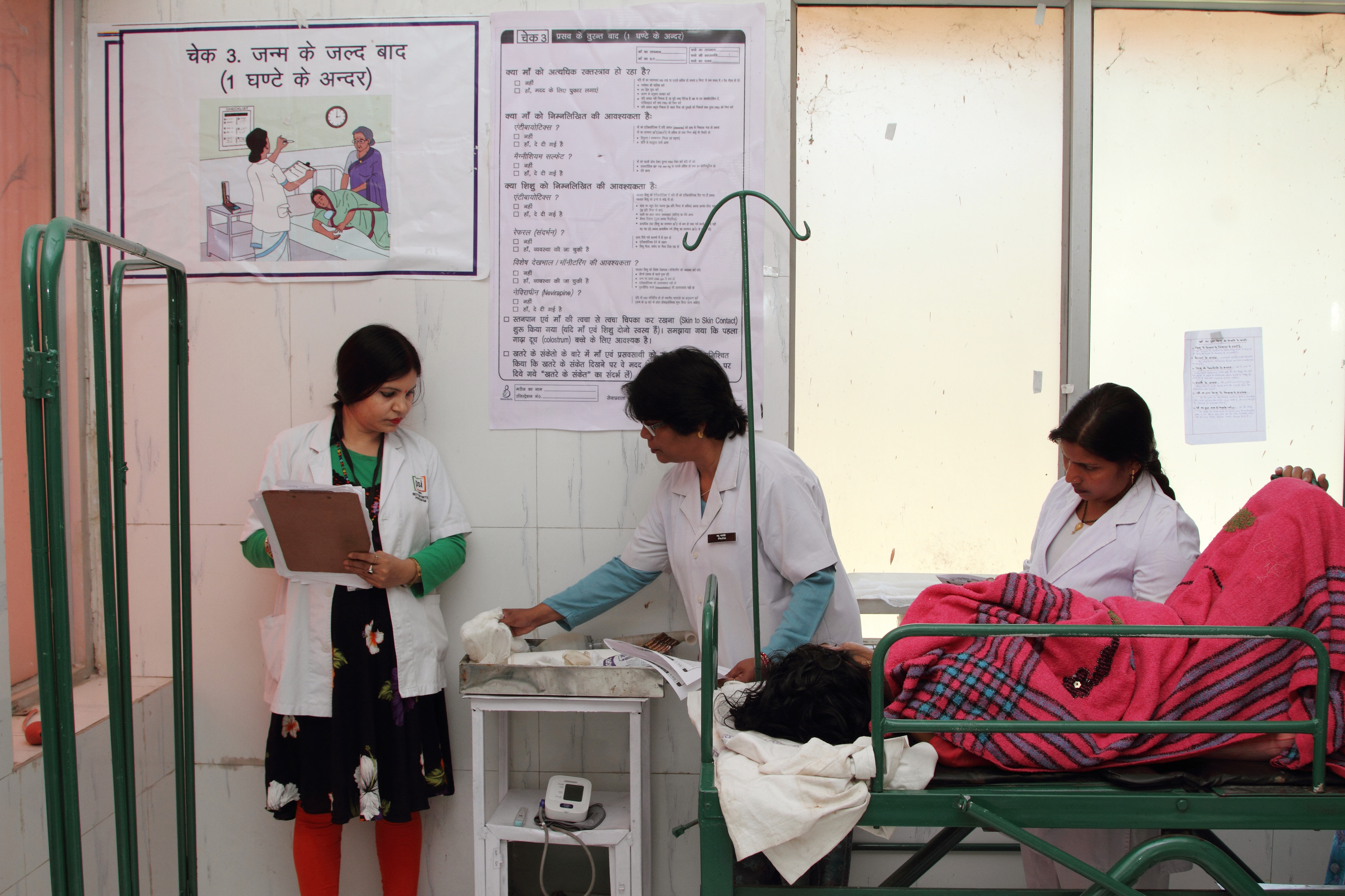 Birth attendants and a BetterBirth coach use the Safe Childbirth Checklist, hanging on the wall, at a facility in Uttar Pradesh to ensure quality care the new mother and baby.