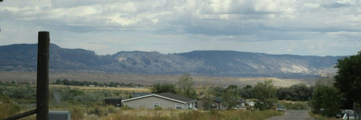 Scenic view of rural Utah with mountains and clouds in the distance.