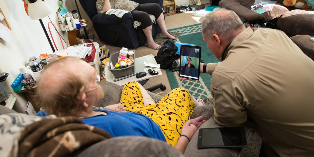 Mock patient and paramedic speak with clinician on a tablet in the patients living room in rural Utah