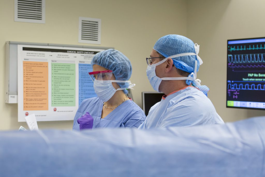 Surgeons prepare for an operation with the checklist in the background