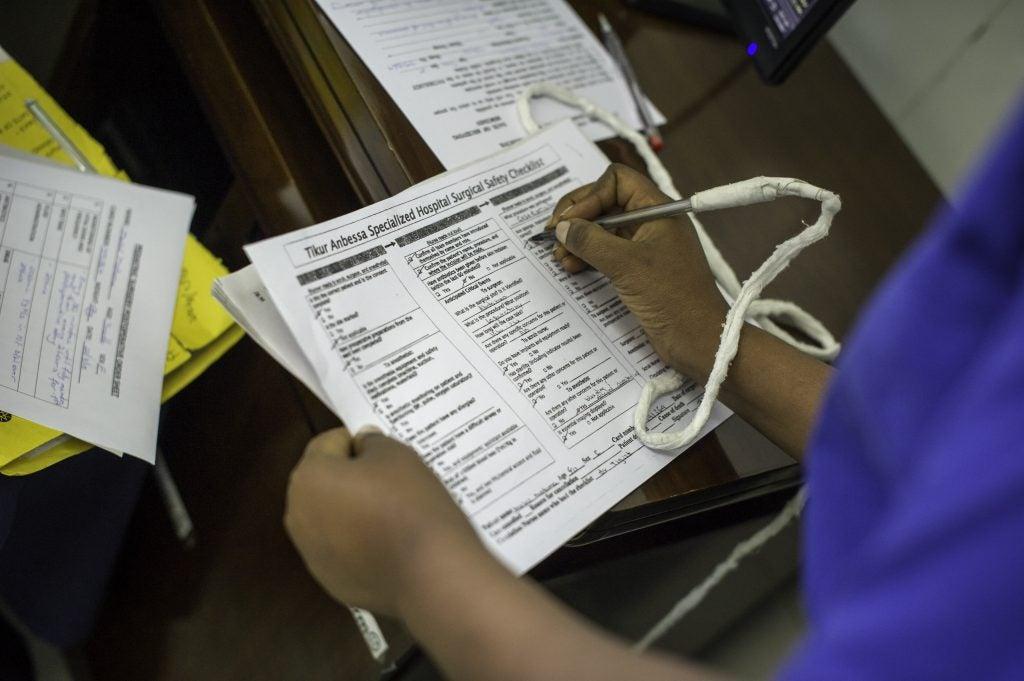 A staff member checks off items on a checklist
