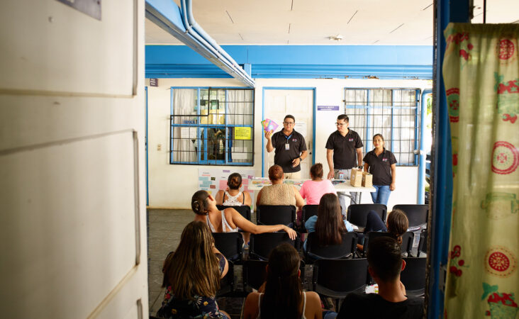 Medical workers give a presentation on reproductive health to a group of young adults.