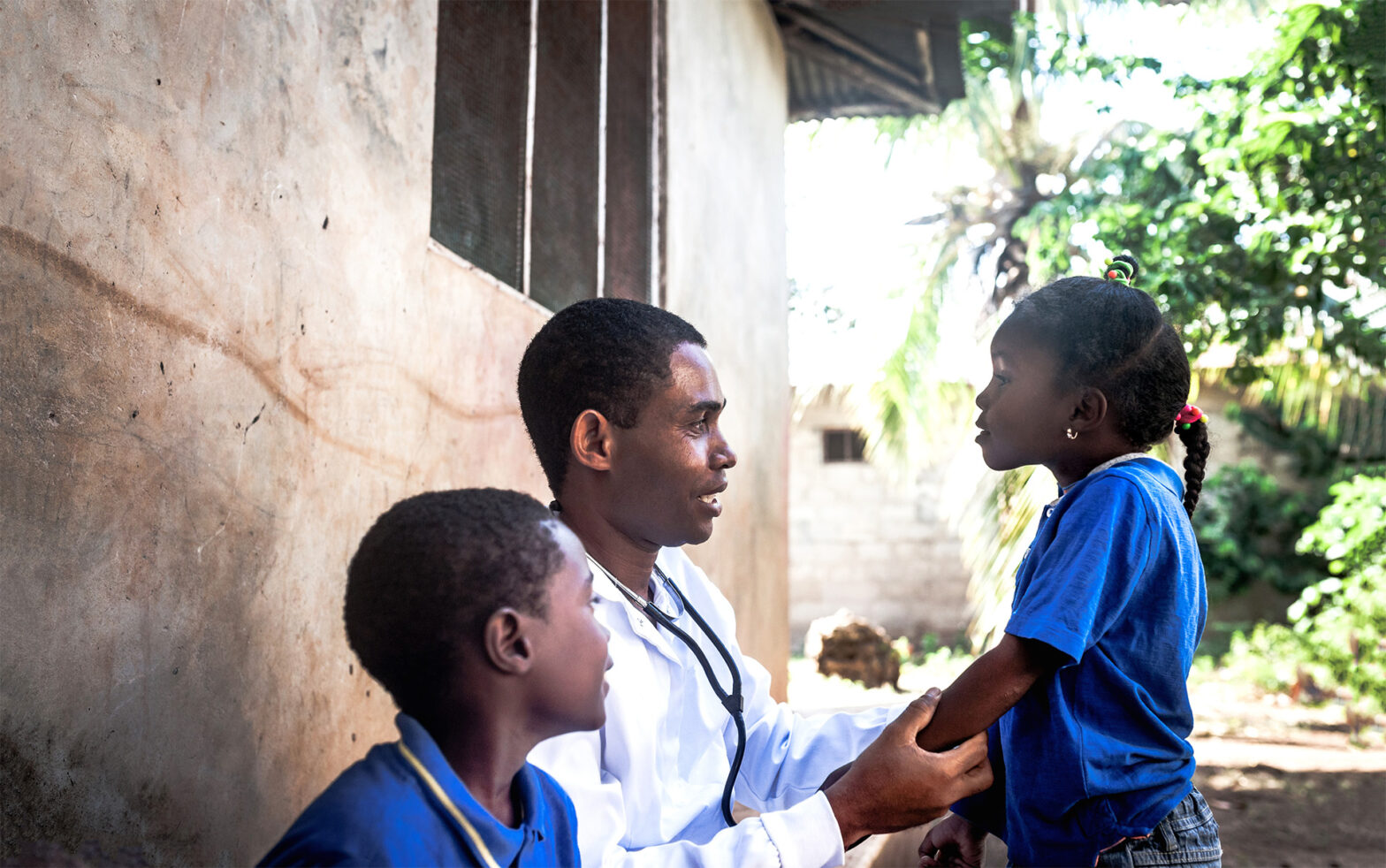 A doctor with two children in Africa.