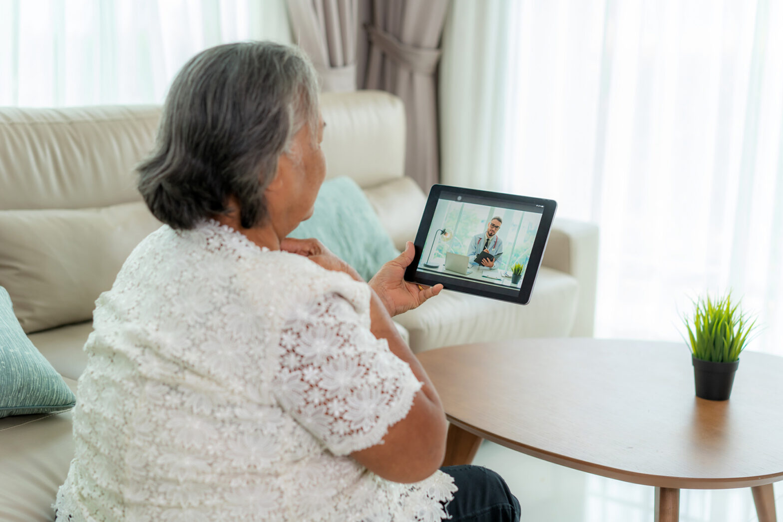 Elderly woman making video call with her doctor from home.