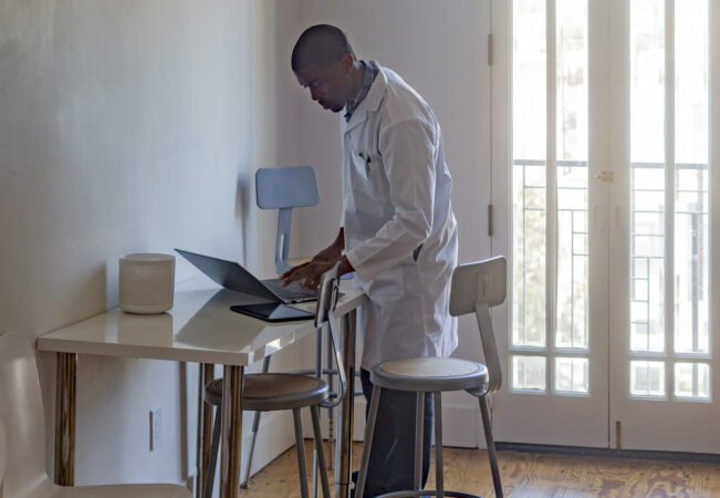 Doctor standing at a desk using a laptop.